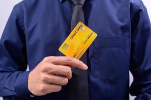 homem segurando um cartão de crédito amarelo