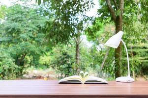 livro e lâmpada na mesa do lado de fora