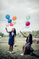 namoradas felizes segurando balões multicoloridos em um parque