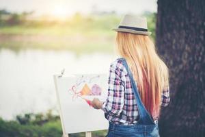 jovem faz um desenho no parque foto