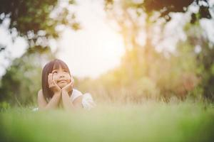 menina deitada confortavelmente na grama e sorrindo foto