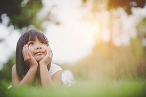 menina deitada confortavelmente na grama e sorrindo