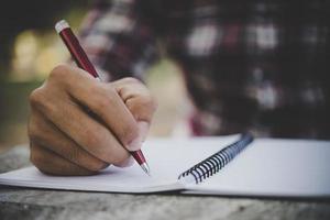 homem escrevendo a mão em seu caderno