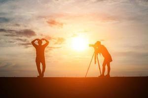 silhueta de um fotógrafo com modelo e câmera ao pôr do sol
