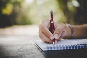 homem escrevendo a mão em seu caderno foto