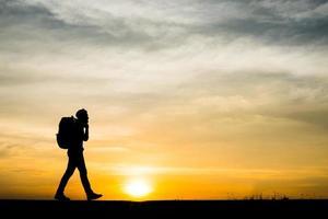 silhueta de um jovem mochileiro caminhando durante o pôr do sol
