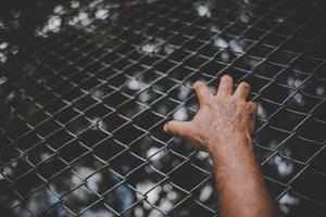 mão na cerca de metal, sem sentir liberdade