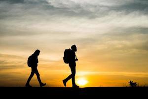silhuetas de dois caminhantes com mochilas apreciando o pôr do sol