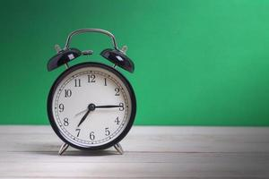 despertador na mesa com fundo verde