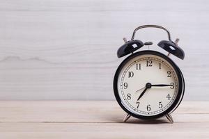 relógio preto na mesa de madeira foto