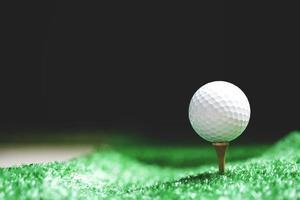 close-up da bola de golfe no tee à noite