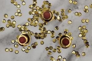 três batons e lantejoulas douradas foto