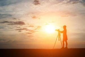 silhueta de um fotógrafo fotografando ao pôr do sol