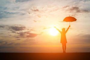silhueta de uma mulher segurando um guarda-chuva na praia e no pôr do sol