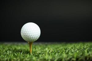 bola de golfe no tee à noite