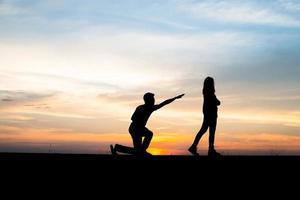 silhueta de um casal chateado em uma briga ao pôr do sol foto