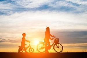 mãe com seu filho andando de bicicleta ao pôr do sol
