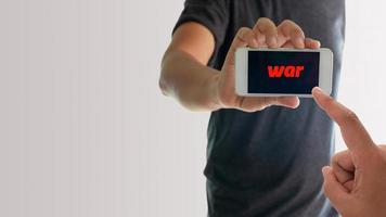 homem segurando telefone com guerra na tela