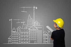 menino usando um chapéu amarelo de engenheiro e idéias de planos de casa no quadro-negro
