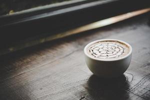 uma xícara de café em uma mesa de madeira foto