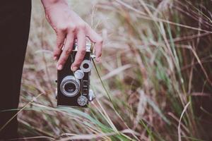 close-up da mão de uma jovem segurando uma câmera retro em um campo
