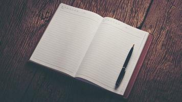 imagem de um caderno em branco aberto na mesa de madeira
