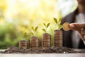mãos juntando pilhas de moedas de dinheiro na natureza foto