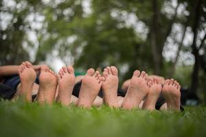 close-up dos pés da família juntos em um campo verde foto