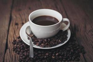 xícara de café com grãos de café em uma mesa de madeira foto