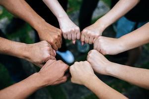 close-up de grupo multiétnico em pé com as mãos juntas foto