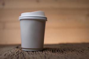 xícara de café de papel em branco na mesa de madeira foto