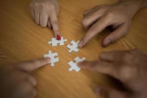 mãos conectando a peça do quebra-cabeça na mesa de madeira foto