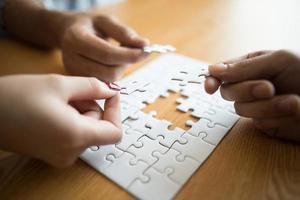 mãos conectando a peça do quebra-cabeça na mesa de madeira