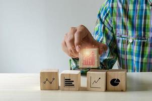 mão empilhando blocos de madeira com ícones de negócios