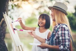 mãe e filhas fazendo desenhos juntas em um parque
