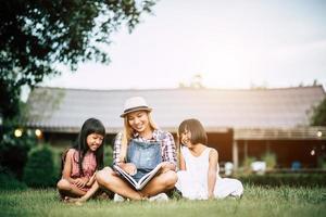 mãe contando uma história para suas duas filhas pequenas na horta foto