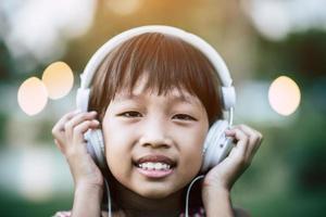 menina ouvindo música no parque com fones de ouvido