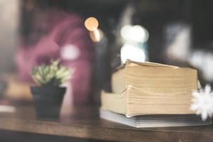 flor de cacto com uma pilha de livros na mesa de madeira