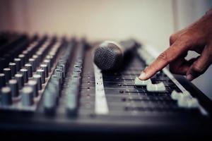mãos do engenheiro de som ajustando o console de mixagem de áudio
