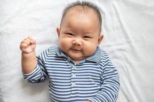 bebê deitado de bruços em uma cama branca e olhando para a câmera foto