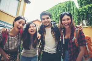 grupo de amigos se encontrando na cidade e sorrindo para a câmera