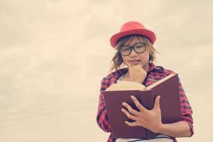 mulher jovem hippie segurando um livro abaixo do céu