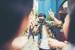 jovem tirando fotos de seus amigos enquanto viajava juntos em uma área urbana