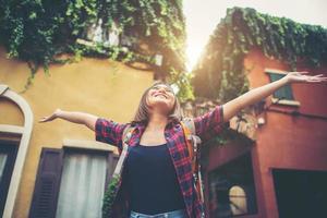 jovem feliz curtindo suas viagens, levantando as mãos no ar foto