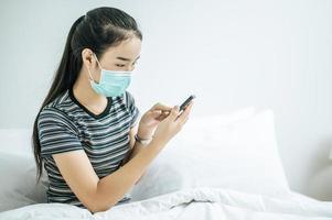 garota usando uma máscara higiênica, camisa listrada e segurando um telefone celular