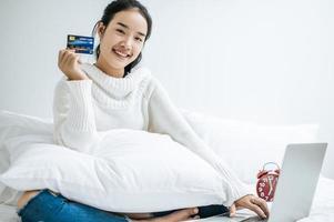 jovem fazendo compras no laptop e segurando um cartão de crédito