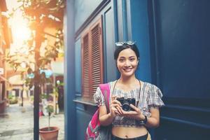 retrato de mulher jovem e hippie se divertindo na cidade com a câmera