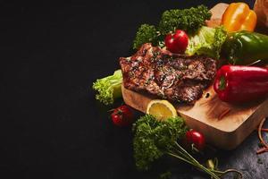 bife e legumes em fundo escuro foto