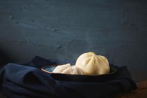 pães cozidos no vapor em fundo escuro foto