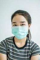 uma mulher vestindo uma camisa listrada e uma máscara protetora